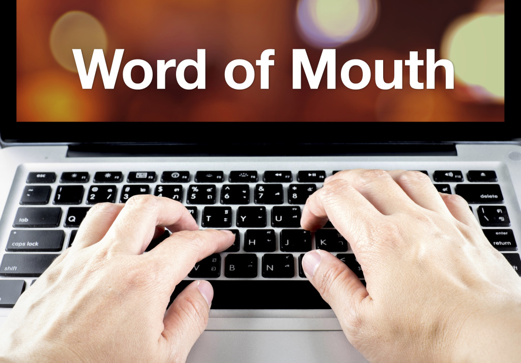 Word of mouth word on notebook screen with hand type on keyboard